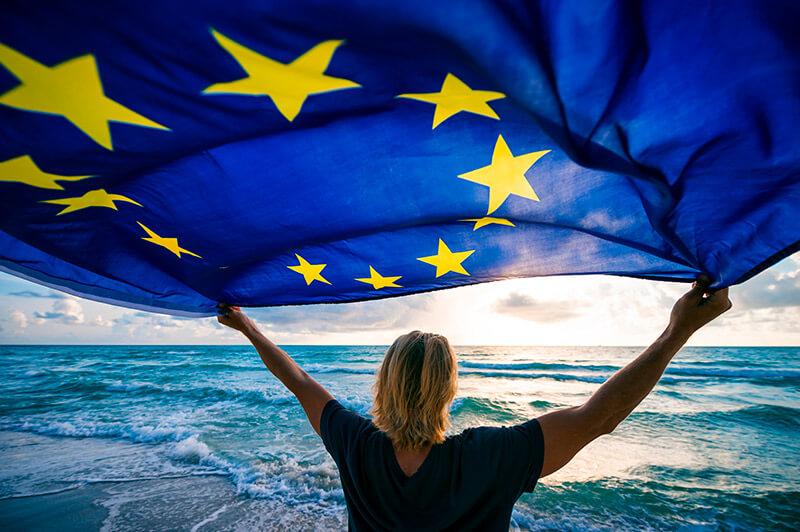 Man holding EU European Union flag waving in front of Mediterranean sunrise seascape